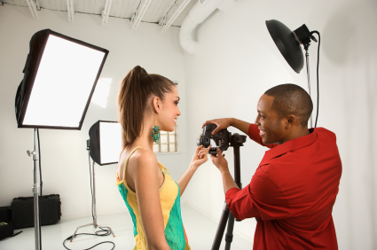 Young African American male adult and Caucasian young female adult at Models Direct previewing image on digital camera.